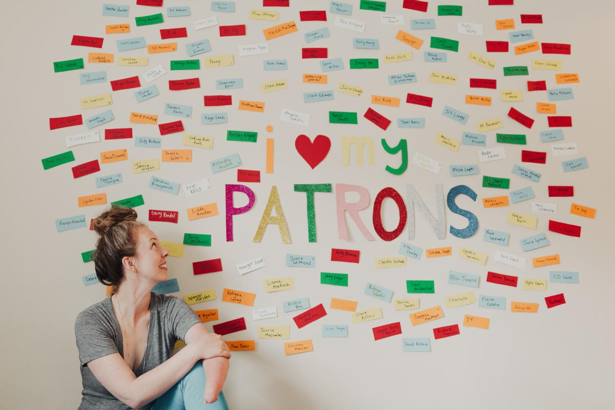 Alexis Hillyard in front of her wall with the names of Patreon supporters
